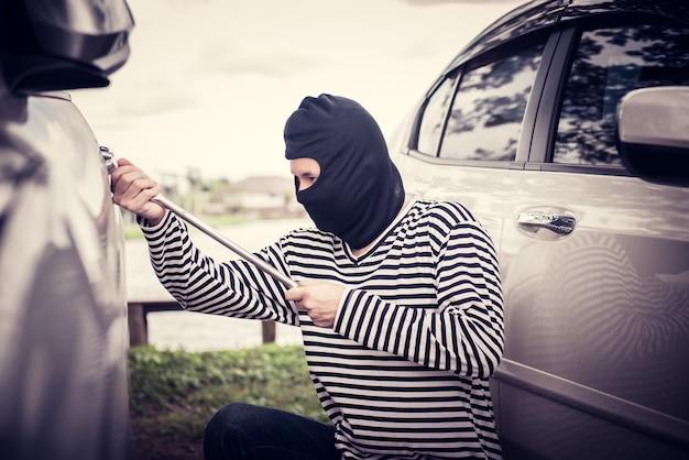 Ladrão está tentando roubar o carro no estacionamento público