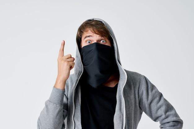 Ladrão hacker com máscara preta e capuz em um espaço claro