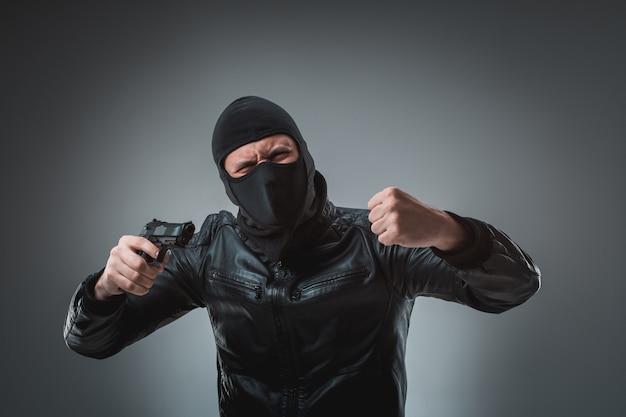 Ladrão mascarado com arma, olhando para a câmera.