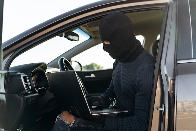 Ladrão mascarado em uma balaclava roubando laptop do carro e olhando para a tela enquanto está sentado lá dentro. conceito criminoso. foto