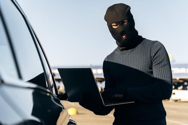 Ladrão mascarado em uma balaclava roubando laptop do carro e segurando-o aberto enquanto estava perto do carro. conceito criminoso. foto