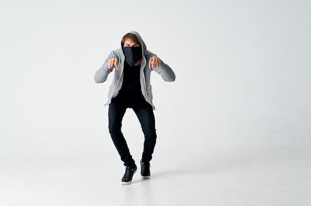 Ladrão masculino com capuz máscara escondida fundo isolado na ponta dos pés