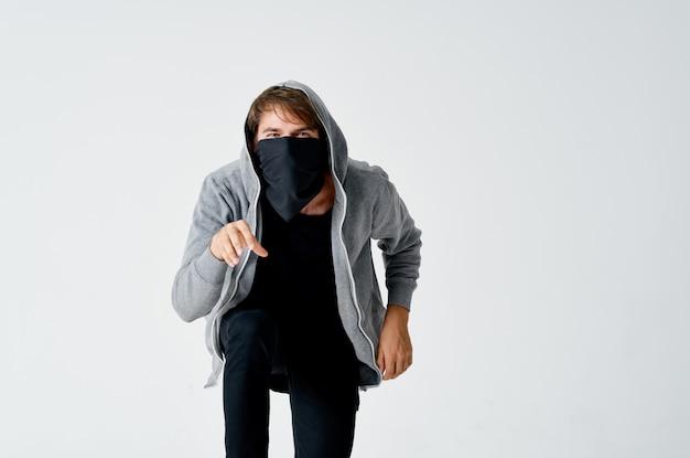 Ladrão masculino com capuz máscara escondida fundo na ponta dos pés