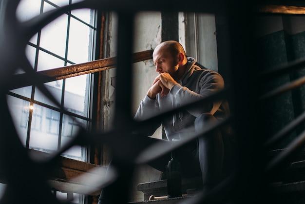 Ladrão masculino com garrafa de álcool se senta na escada. ladrão de rua esperando pela vítima. conceito de crime