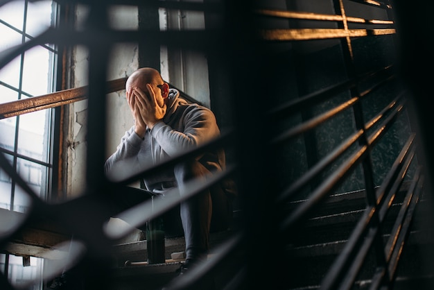 Ladrão masculino com garrafa de álcool sentado na escada