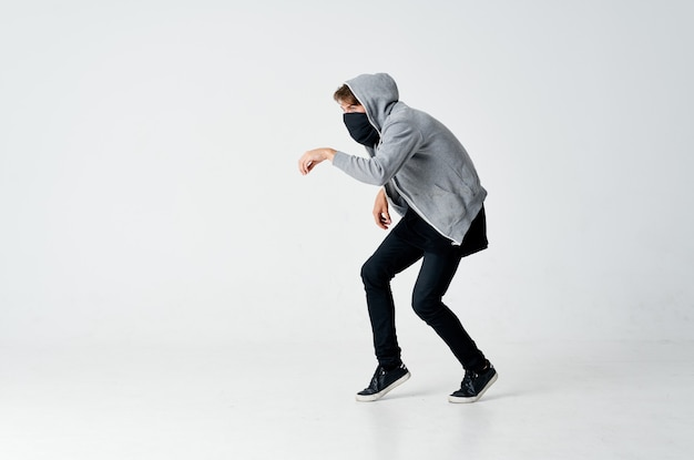 Ladrão masculino com máscara oculta de capuz na ponta dos pés
