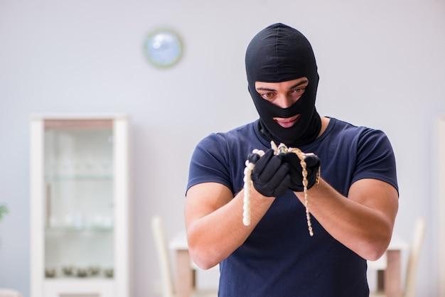 Ladrão usando balaclava roubando coisas valiosas