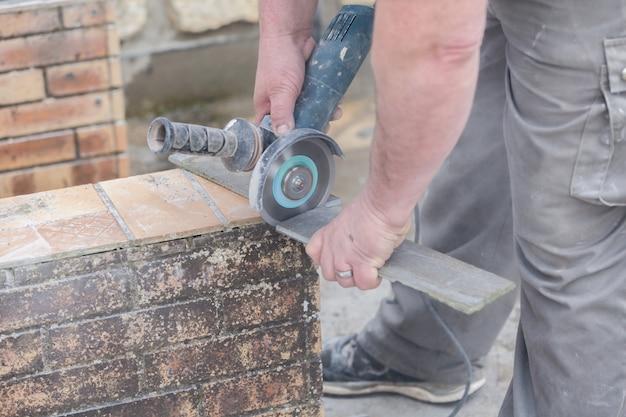Ladrilhador cortando uma telha com um moedor