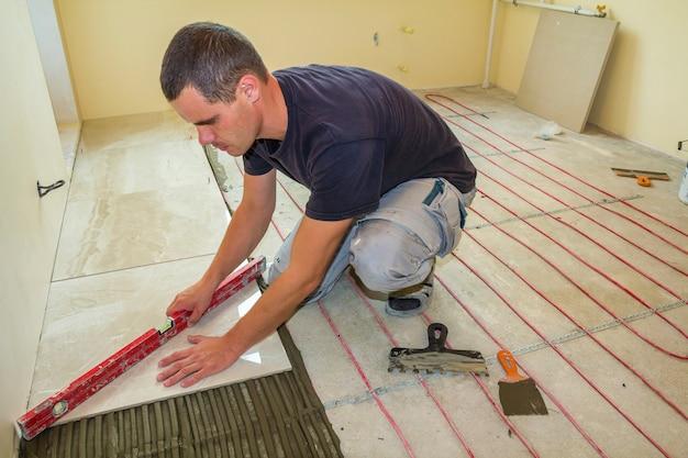 Ladrilhador de jovem trabalhador instalar telhas cerâmicas no chão de cimento