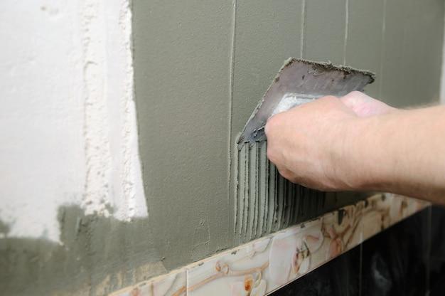 Ladrilhadores mãos estão colocando um adesivo
