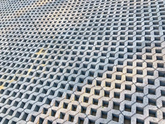 Ladrilho de bloco de tijolo de pedra de cor cinza com grama verde e areia como plano de fundo ou textura.