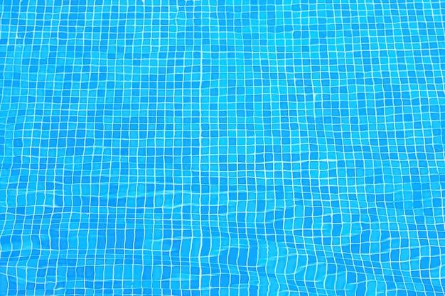 Ladrilhos azuis no fundo da piscina. ondulações distorcendo o revestimento de azulejos azuis de uma piscina. piscina com vista superior