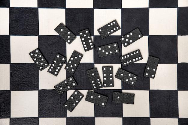 Ladrilhos de dominó pretos espalhados aleatoriamente em um tabuleiro de xadrez preto e branco