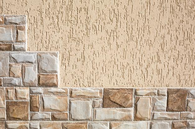 Ladrilhos de pedra em forma de degraus em fragmentos retangulares de cor bege e areia e gesso na parede com padrão de casca de árvore.