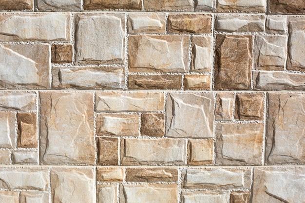 Ladrilhos de pedra feitos de fragmentos retangulares de cor bege e areia. fundo, textura.