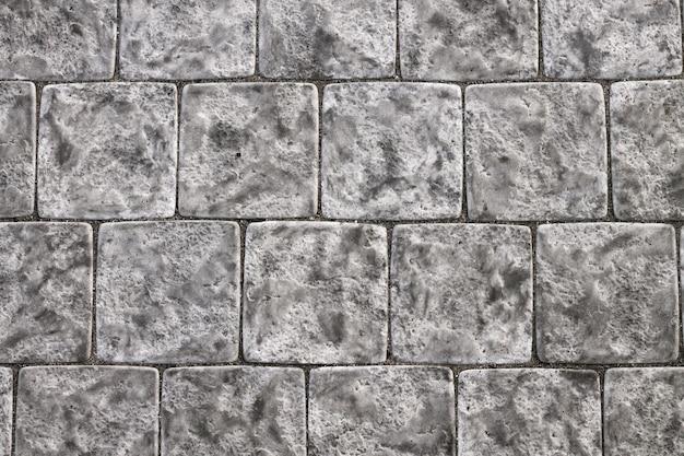 Ladrilhos quadrados de pedra cinza com textura de costuras