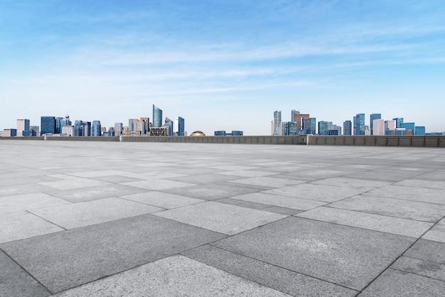 Ladrilhos quadrados vazios e linha do horizonte de edifícios urbanos