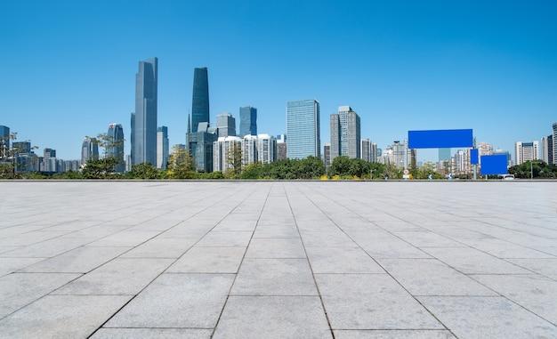 Ladrilhos vazios e linha do horizonte de edifícios da cidade