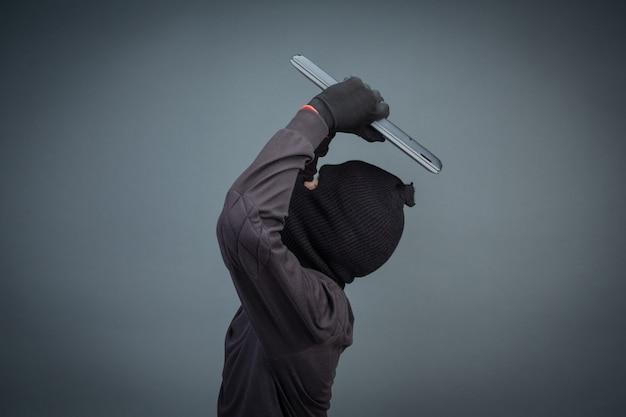Ladrões masculinos roubam um computador portátil em cinza