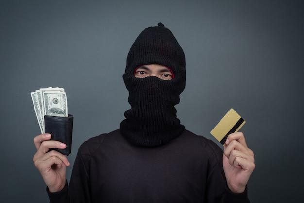 Ladrões seguram cartões de crédito usando um laptop para atividades de hacking de senhas.