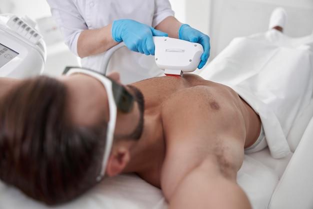Lady cosmetologista com luvas azuis faz a depilação do peito do cliente com equipamento a laser moderno