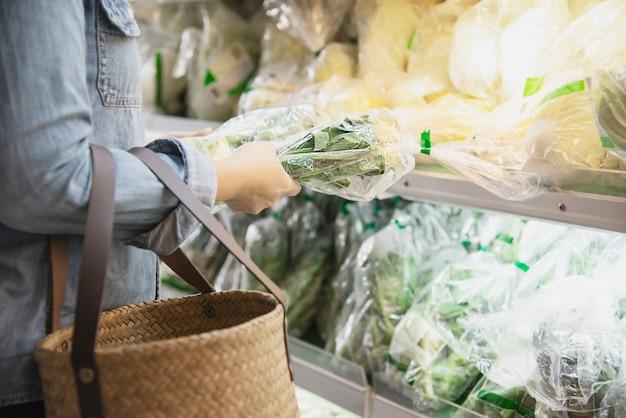 Lady está comprando vegetais frescos na loja de supermercado