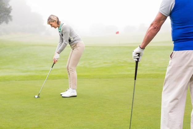 Lady golfista teeing fora para o dia assistido pelo parceiro