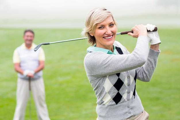 Lady golfista vai sair para o dia visto pelo parceiro