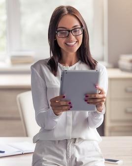 Lady in eyeglasses está usando um tablet digital.