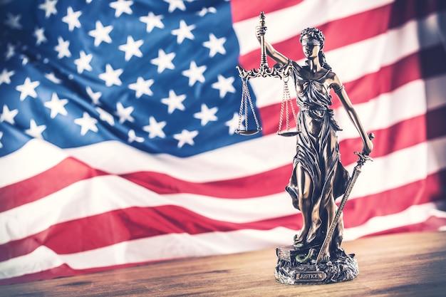 Lady justice e a bandeira americana. símbolo da lei e da justiça com a bandeira dos eua