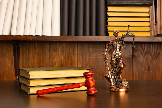 Lady justice, martelo do juiz, livros em uma velha mesa de madeira