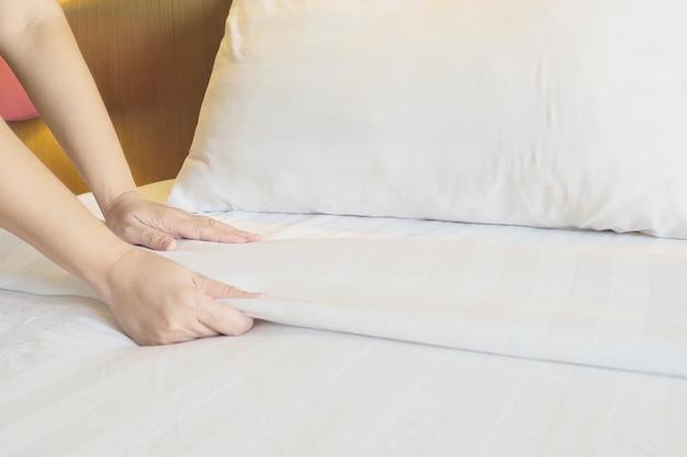 Lady mãos configurar lençol branco no quarto de hotel