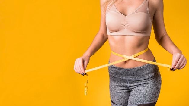Lady medindo a cintura por fita