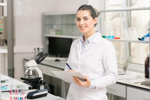 Lady pesquisador fazendo anotações sobre produtos químicos