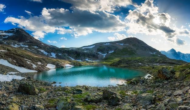 Lago alpino com a última neve no verão
