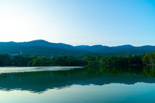Lago ang kaew na universidade de chiang mai com montanha arborizada e céu crepuscular