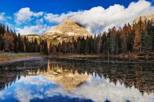 Lago antorno nas dolomitas e com incrível reflexo do céu nublado e montanha rochosa, tirol do sul, itália
