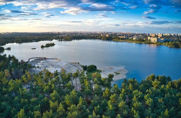 Lago azul, floresta de pinheiros, cidade grande e lindo céu com nuvens em uma foto
