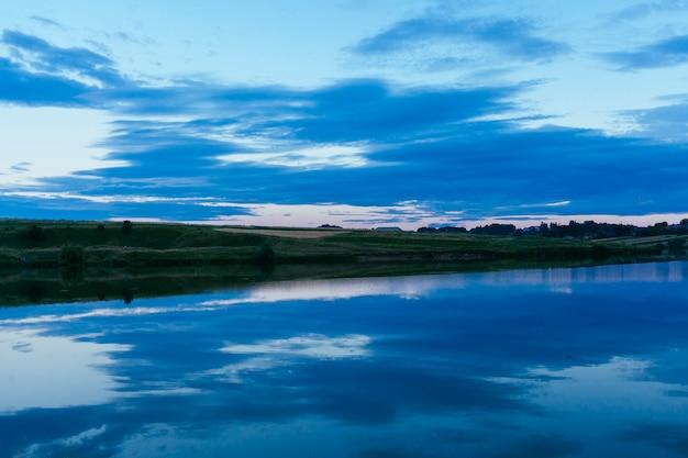 Lago azul lindo com reflexo do céu