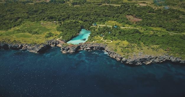 Lago azure na costa de rocha verde na baía do mar em vista aérea