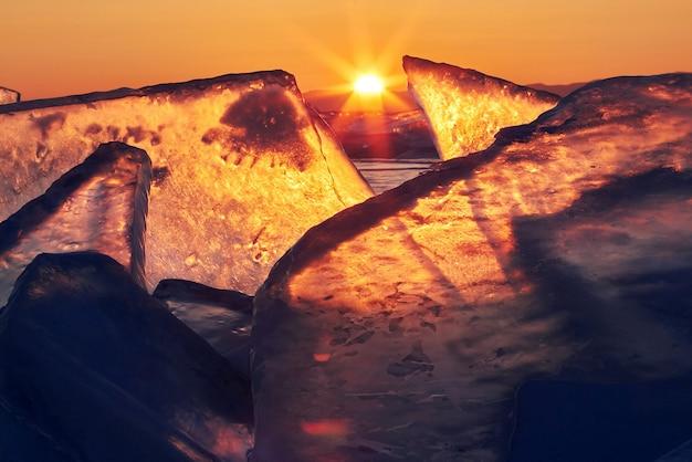 Lago baikal ao pôr do sol, tudo está coberto de gelo e neve, gelo azul claro e espesso. lago baikal sob os raios do sol poente. lugar incrível, patrimônio mundial da unesco
