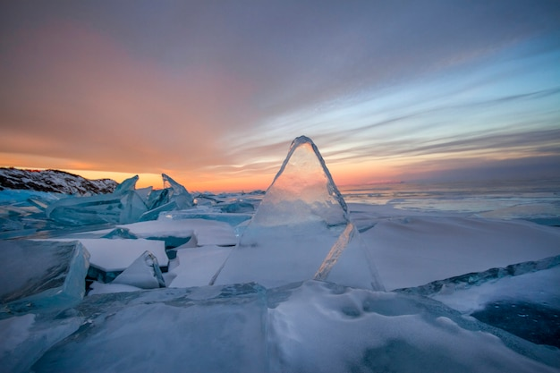 Lago baikal ao pôr do sol, tudo está coberto de gelo e neve, gelo azul claro e espesso