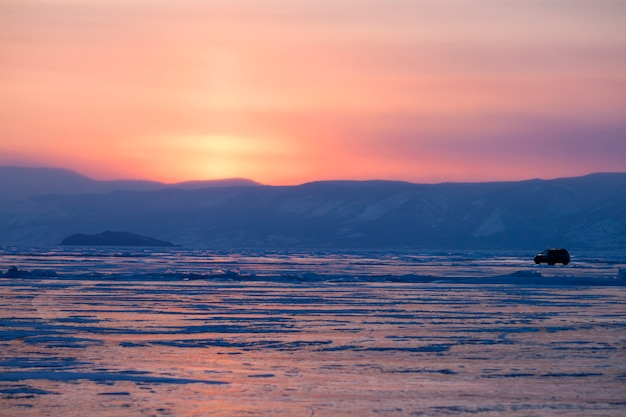 Lago baikal congelado. pôr do sol. carro