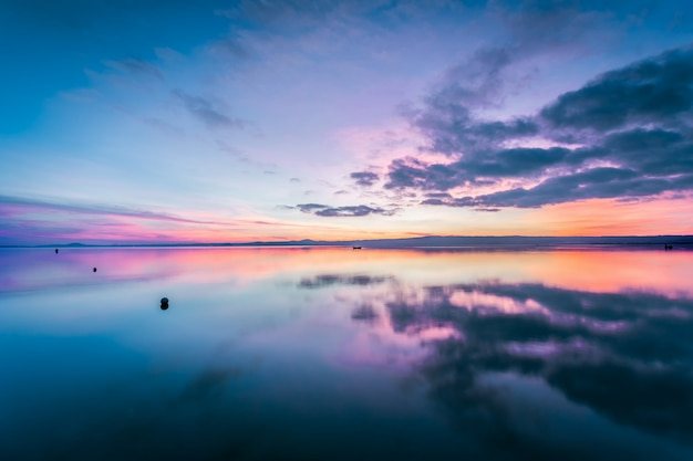 Lago bolsena ao pôr do sol. um lugar maravilhoso rodeado pela paisagem do lácio. é o maior lago vulcânico da europa.