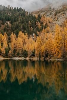 Lago calmo e nuvens baixas que cobrem uma montanha áspera coberta com folhagem colorida de outono