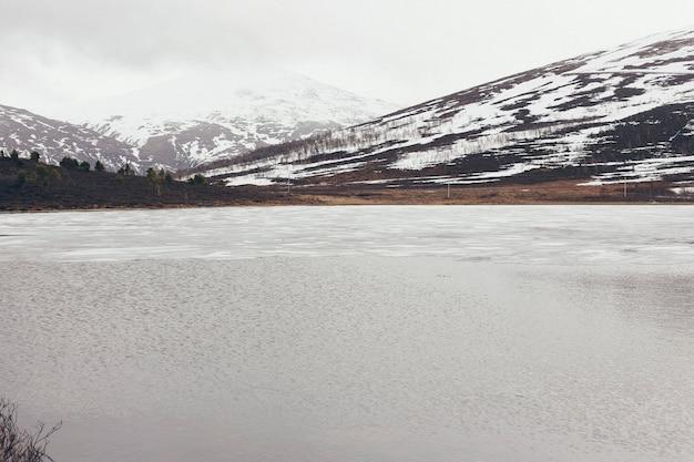 Lago cercado por altas montanhas nevadas no inverno.