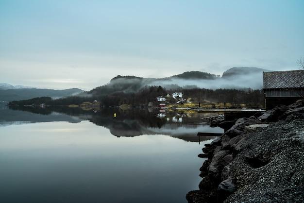Lago cercado por colinas cobertas de névoa com a vegetação refletindo na água