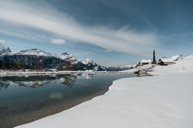 Lago cercado por pedras e casas cobertas de neve sob o sol