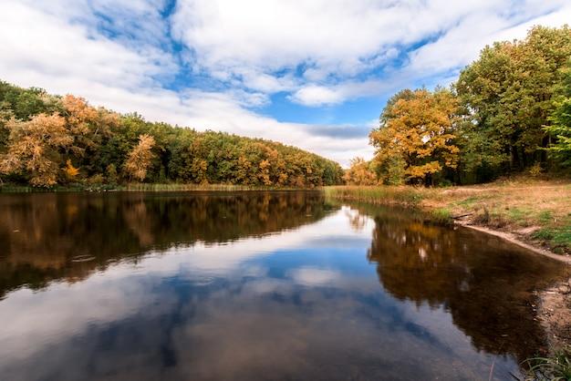 Lago com árvores de outono na costa. a superfície do espelho do lago.