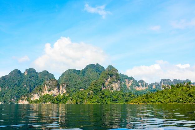 Lago com montanhas, floresta e paisagem de céu nublado